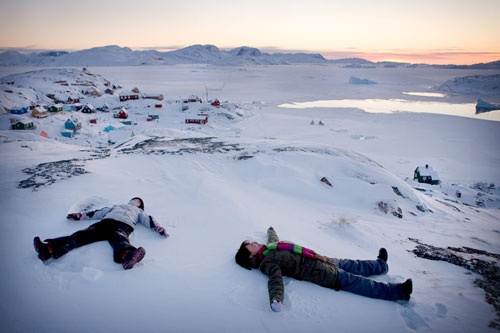 Children making angels in the snow on the hilltop of the tiny village of Aappilattoq, West Greenland.