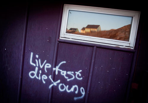 Graffiti on a house wall in Ilulissat that reads Live fast die young