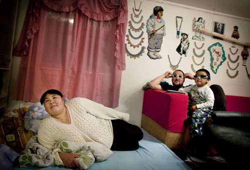 Ella, Salu, and their son Hans, four, watching a 3-D movie in their home in Isortoq.