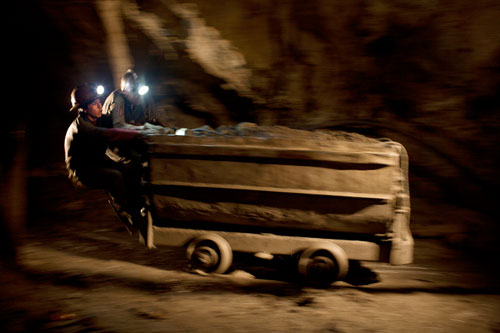 German Flores, seventeen, and Emiliano Mamani, twenty-four, ride a cart full of minerals to the exit of Candelaria Mine.