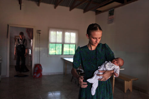 Maria Peters, fifteen, holds her newborn baby sister at their home in the Mennonite settlement of Manitoba, in eastern Bolivia.
