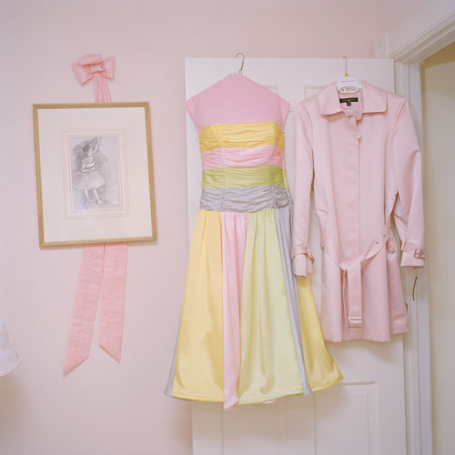 A close cropped shot of the open door of a pink room.  There is a pink ribbon on the wall behind a framed picture, and from the door hangs a pink and yellow sun dress on a hook and a pink blouse with matching jacket.