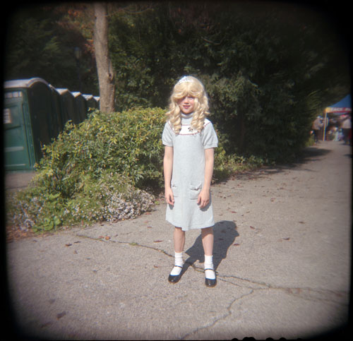 A young blonde girl in a blue sun dress standing, facing the camera, in the middle of a sidewalk.