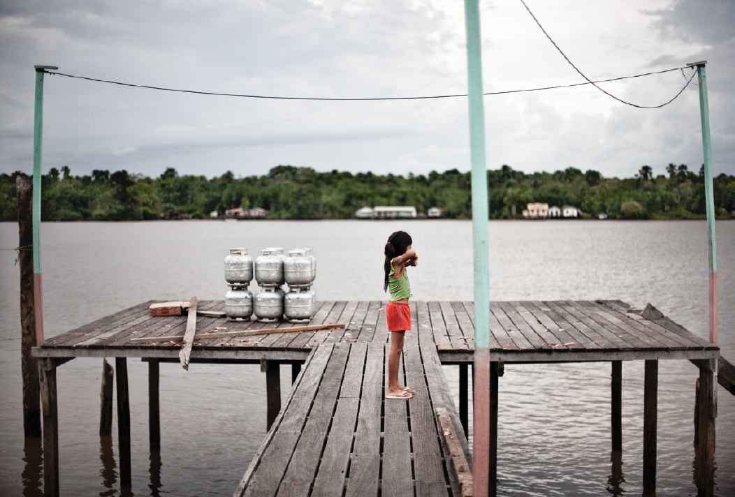 A young girl on the dock in the village of São Francisco da Jararaca, along the Amazon River.