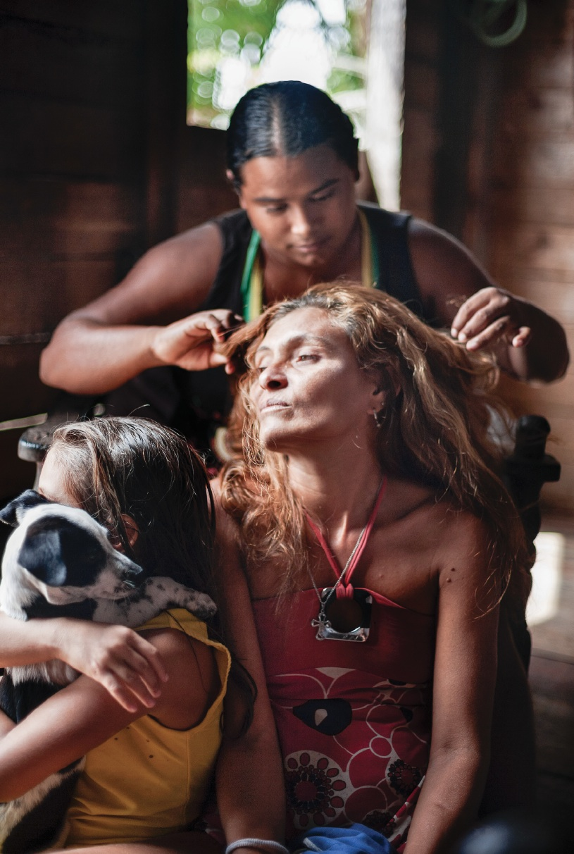 Jamaica picks lice from Nazaré's hair as Nazaré's daughter (L) plays with their new dog. Nazaré sold goods on the cargo ships for some years until her husband Lucevaldo stopped her. Now the family survives on his earnings trading oil.