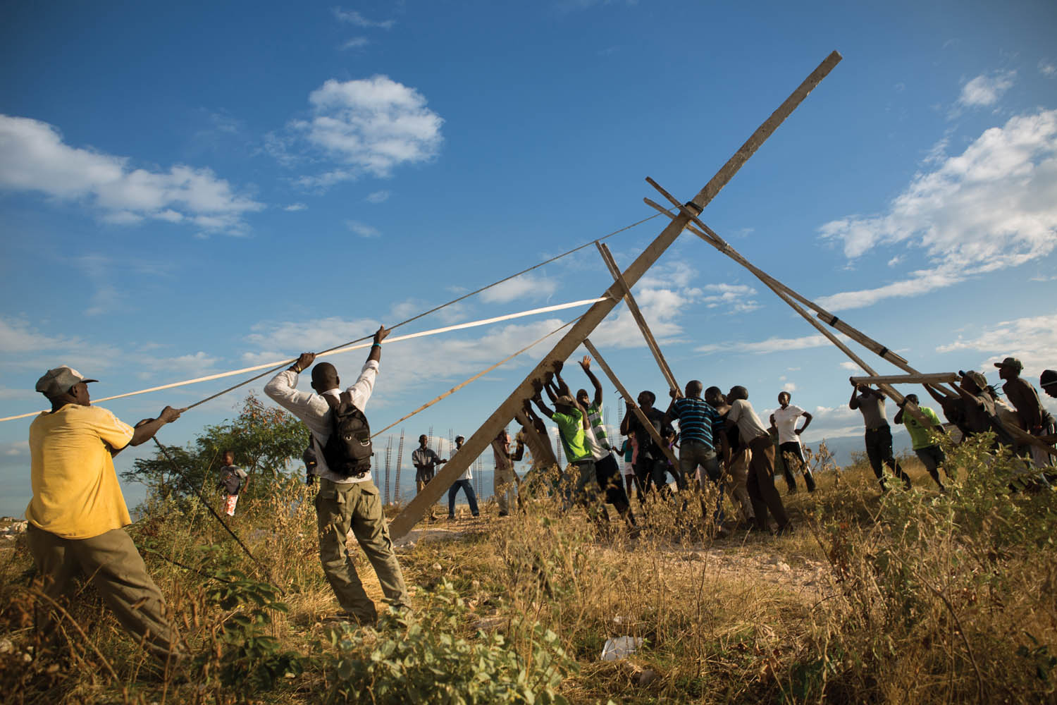 Residents of Canaan raise the first of three handmade utility poles, part of an improvised effort to receive electricity from the state power grid. Photo by Allison Shelley.