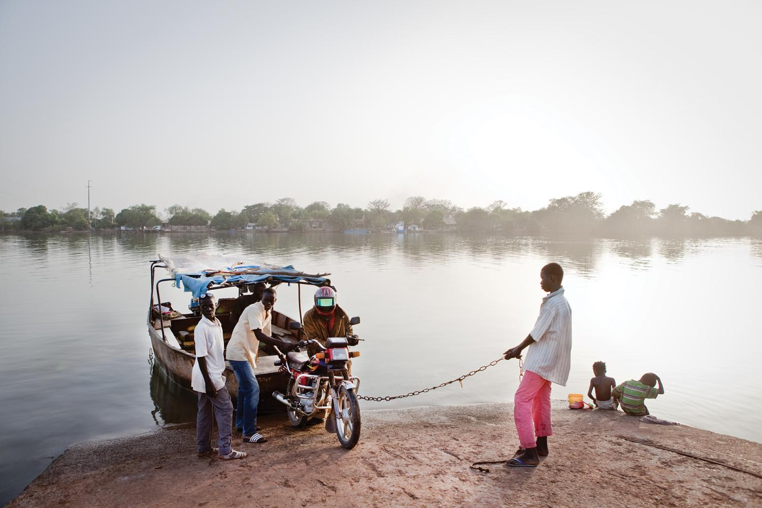 Small metal ferries, called barras, are the main way to cross the Gambia River in the upcountry regions of the Republic of Gambia. Some barras are motorized, but most are rowed with a single paddle attached to the stern.