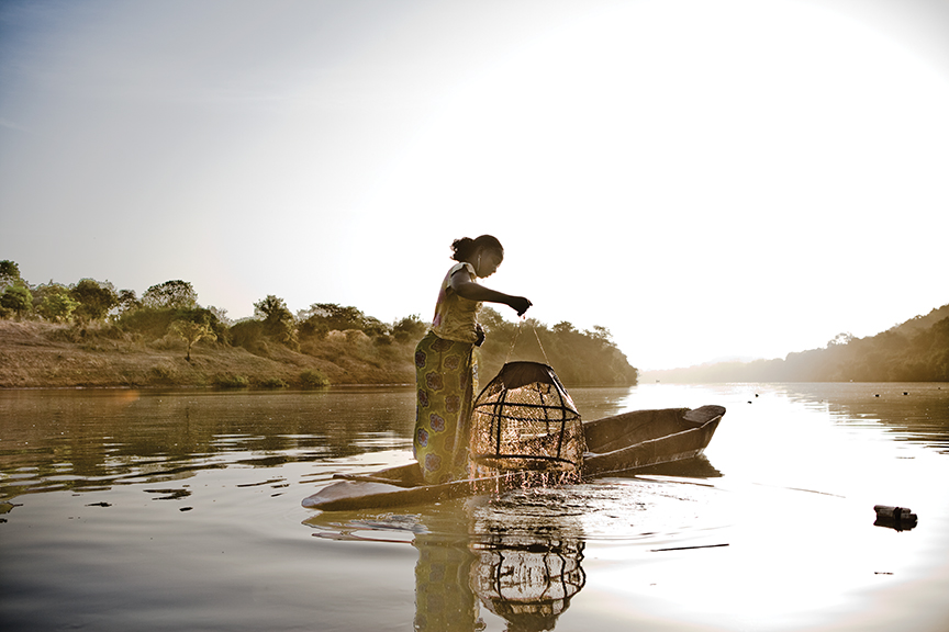 A migrant worker from Mali pulls up fishing pots from the river near the Gambian village of Fatoto.