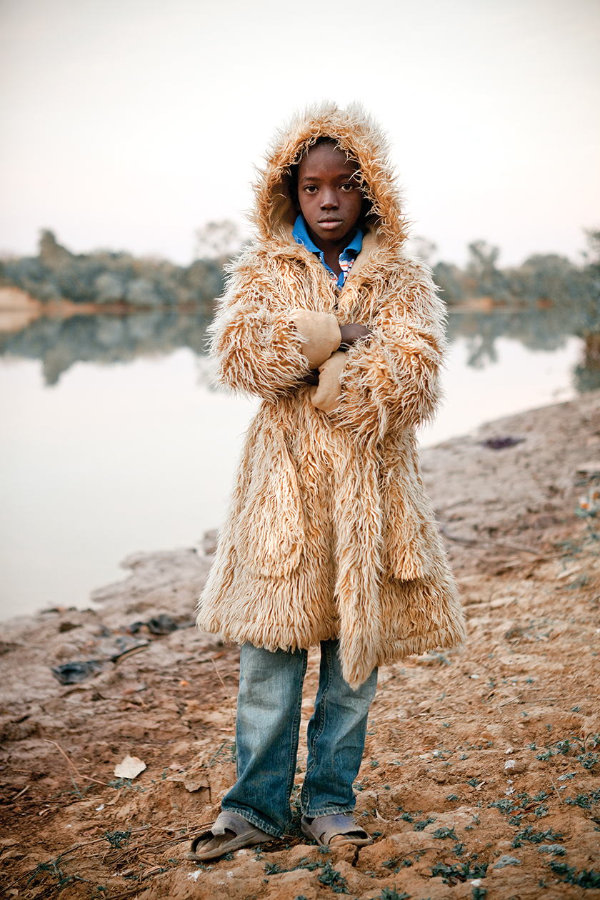 "The son of Bakary Dabo, the Alkalo (village chief) of Diagabu Tenda, wearing a ""fur"" coat on a cool morning."