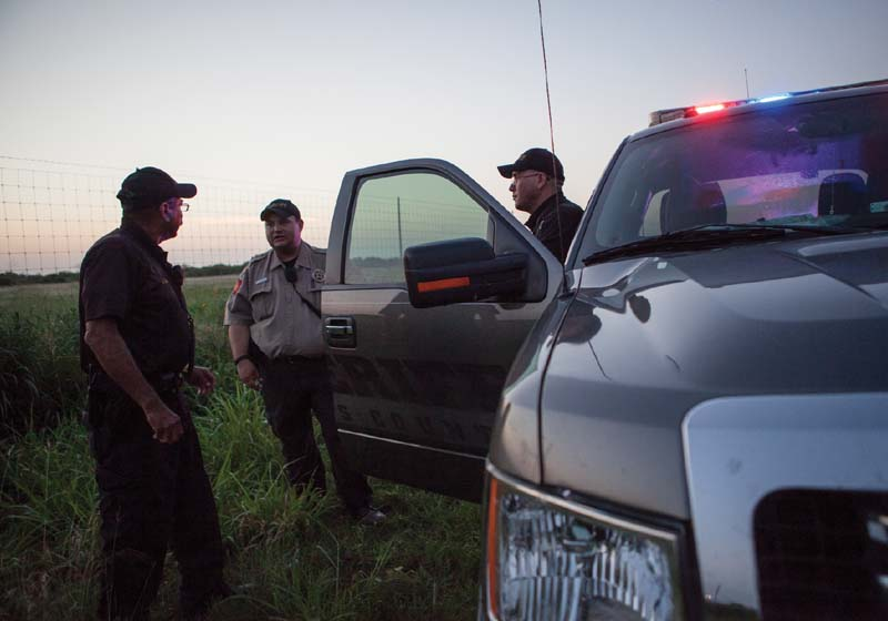 Members of the Brooks County Sheriff's Department meet before searching an abandoned safe house on the outskirts of Falfurrias, Texas.