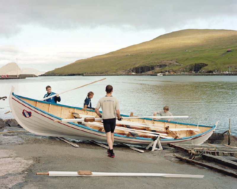 Miðvágur rowers cleaning their boat after practice.