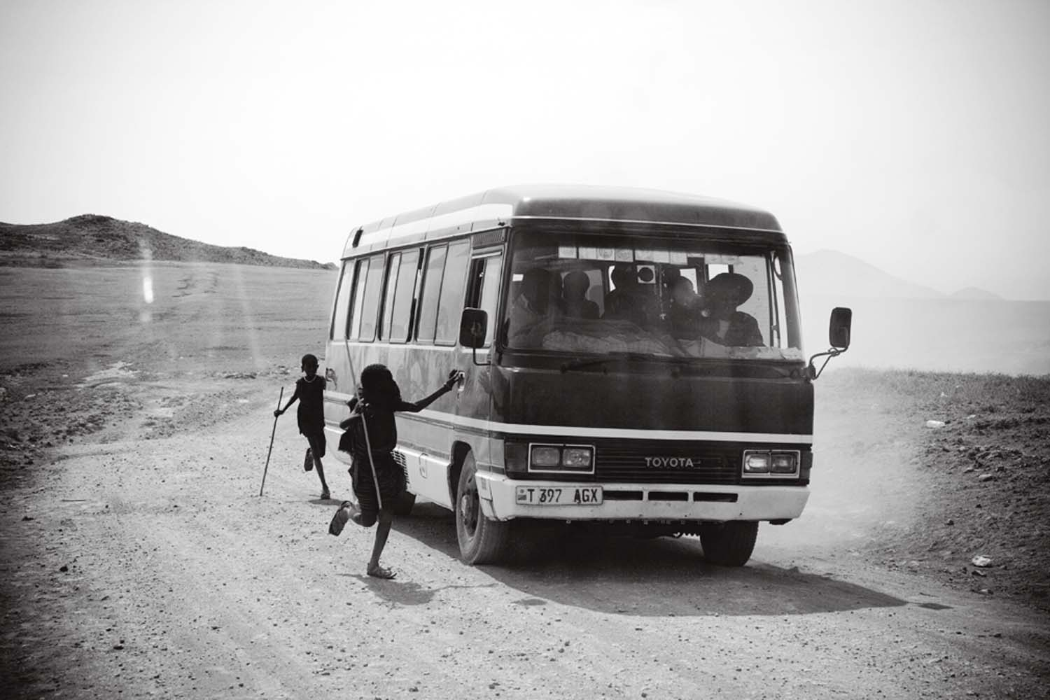 Young Maasai beg for food or change from a bus full of pilgrims on their way to see Reverend Ambilikile Mwasapila, a faith healer in Tanzania's remote district of Loliondo.