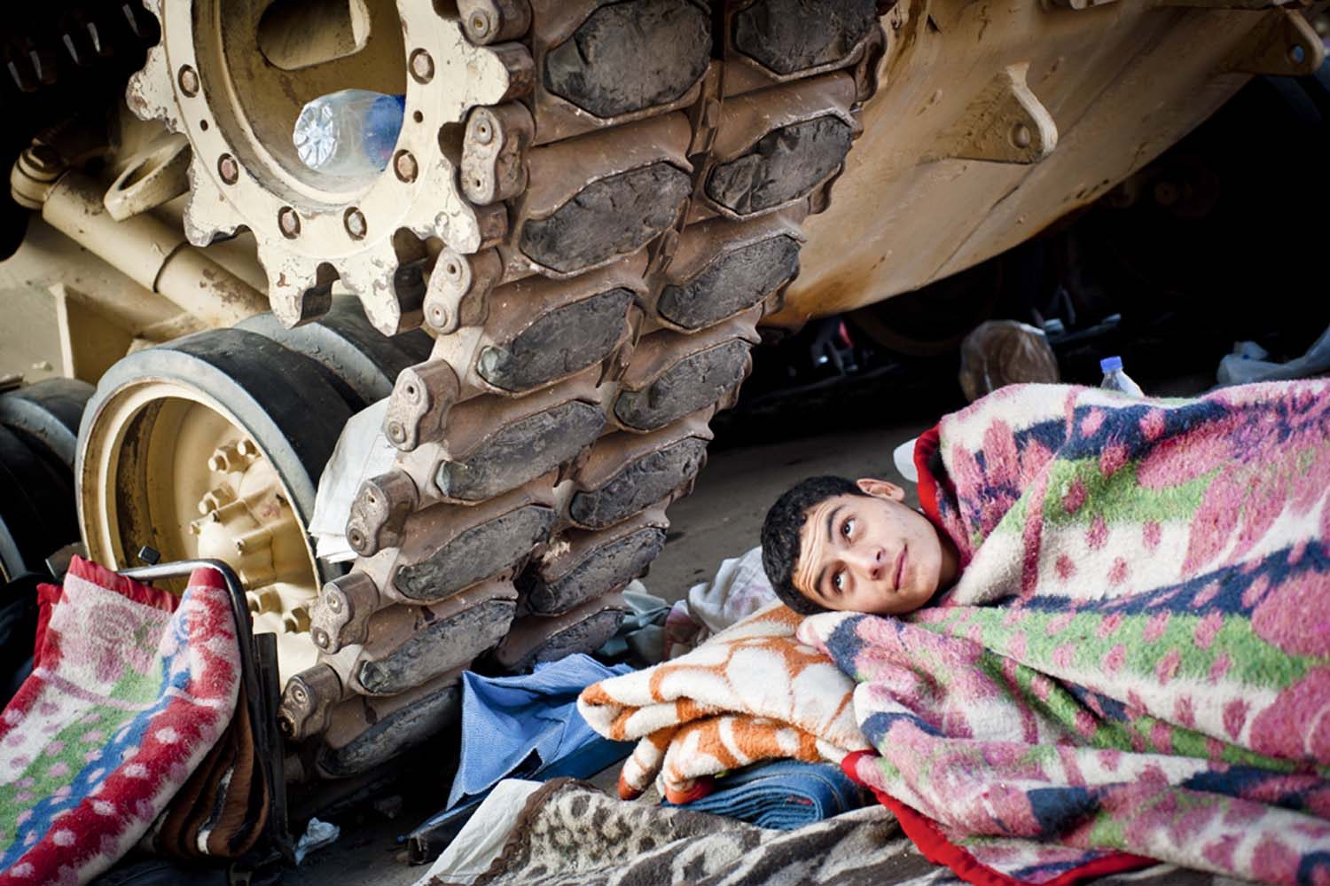 A boy rests under the treads of an Egyptian army tank in Tahrir Square, in downtown Cairo. Protesters gathered there beginning on January 25, 2011, calling for the ouster of President Hosni Mubarak, who had ruled the country unopposed since 1981
