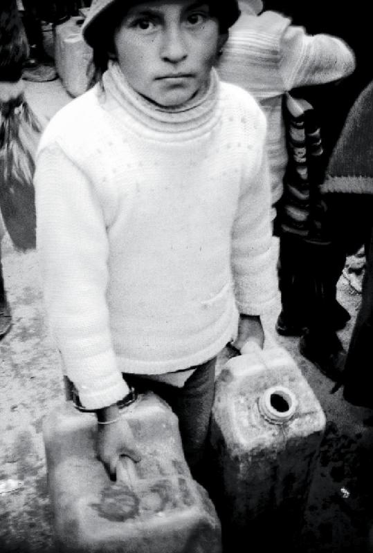 A child sells contaminated water trucked in from a nearby lake.