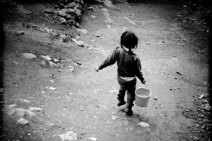 A girl lugs water, hoping to make a sale.