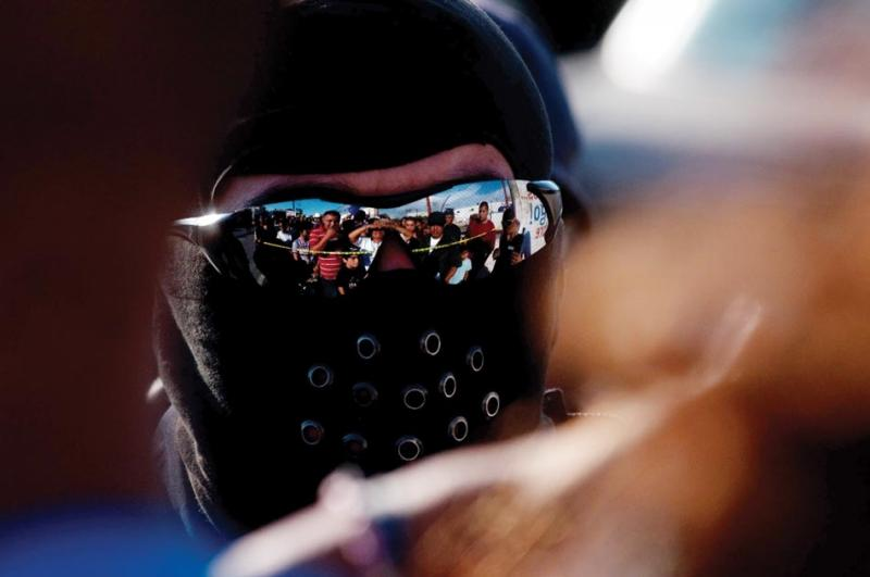A surging, angry crowd reflects in the sunglasses of a masked police officer.