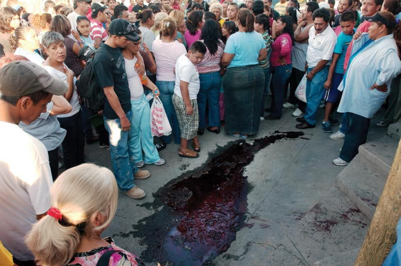 A crowd lingers around the pooled blood of assassinated labor leader Géminis Ochoa, even after his body has been taken away.