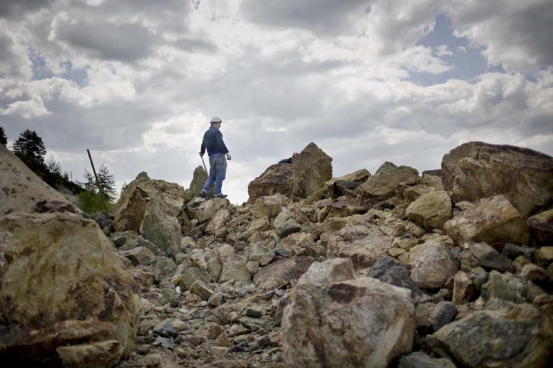 A geologist employed by the Rosia Montana Gold Corporation stands amid the mine's waste-rock rubble. The company has proposed four new open-pit mines, which would generate 200 million tons of waste rock—and bury the nearby village.