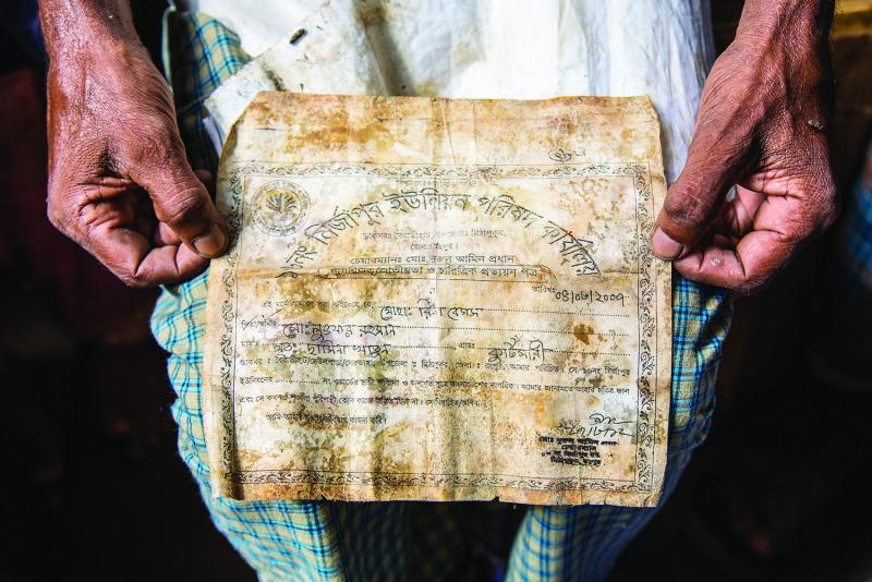 Lutfer Rahman holds the document that his daughter found next to the body of his wife, Rina Rahman, confirming her death in the collapse. (All photographs by Jason Motlagh)