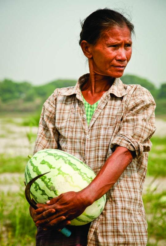 Daw Paw, 52, farmer and grandmother, clutches a water­melon pulled from a seasonal plot her family rents from the government. A small tax is paid on their harvest. Photo by Jason Motlagh.