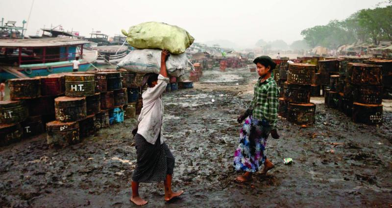 Women laborers off-load sacks of charcoal near the Mandalay jetty. Photo by Jason Motlagh.