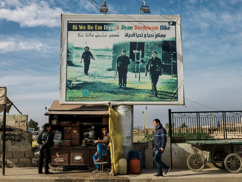 "A billboard in Qamishli, Syria, of martyrs who died while fighting ISIS. The billboard reads, ""With you we live on and life continues."" (Newsha Tavakolian/Magnum Photos)"