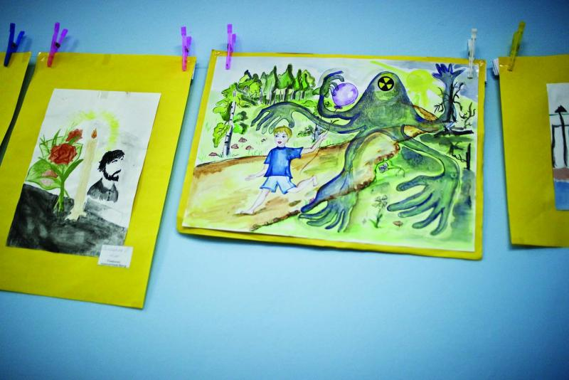 Children's drawings depicting radioactive contamination hang in the daycare activity room of the Social Service Center in Slavutych.