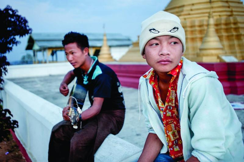 Teenage boys hang out at the pagoda above Layshee, modeled after the famous Shwedagon Pagoda in Yangon.