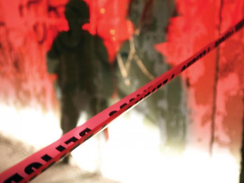 Police tape, marked DANGEROUS, cordons off a murder scene in Juárez, Mexico.