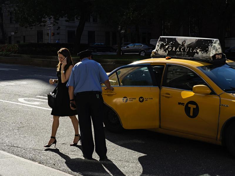 Woman exiting cab, Upper East Side, New York.