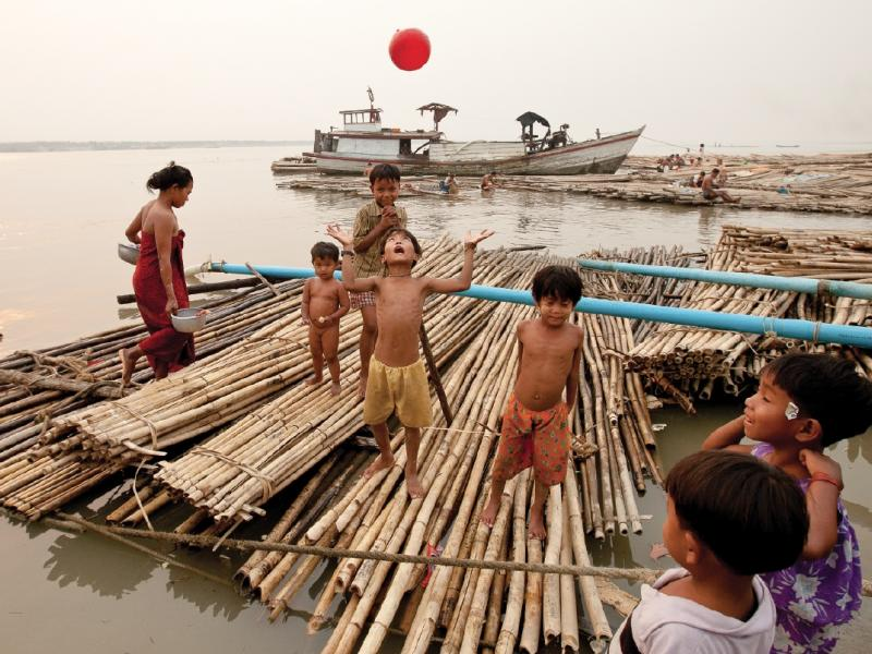 Children play ball on a bamboo raft along the Mandalay quai. Lashed together upriver, the makeshift rafts are floated down to the boomtown and used as construction scaffolding. Photo by Jason Motlagh.
