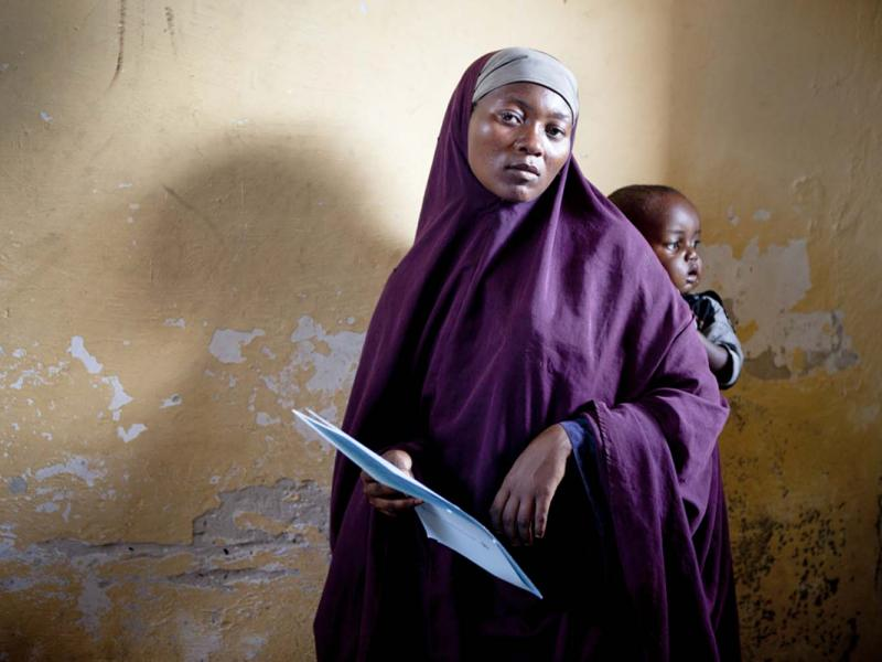 A woman at a clinic in Mogadishu holds the paperwork she will need to complete to receive care for her infant.