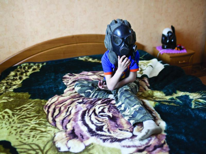 Artiom Mishko plays in his parent's bedroom with a gas mask that is now nothing more than a toy and a relic of a Soviet era that he does not remember.