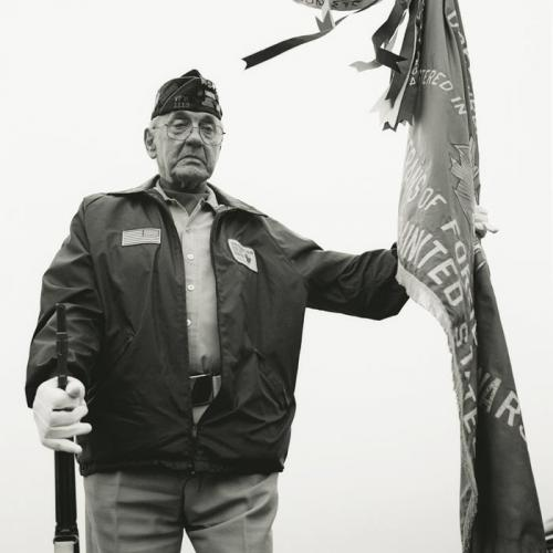 A World War II veteran holds a flag during a service at the Cavalry Cemetery in Eveleth, Minnesota, on Memorial Day, May 26, 2008. Noah Pierce, who is buried there, returned after two tours of Iraq with severe PTSD and committed suicide near his family home on July 26, 2007 (ASHLEY GILBERTSON).